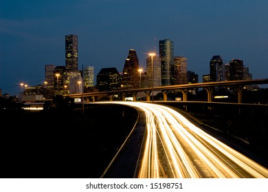 Nighttime traffic out of the city center with skyline and blue sky