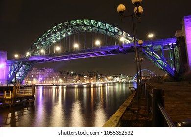 Night-time view of the magnificent Tyne Bridge in Newcastle-Upon-Tyne with the brightly lit quayside and Millennium bridge in background
