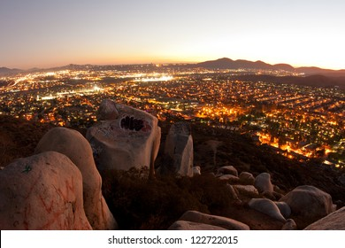 Nighttime view from a mountaintop of big boulders and suburban San Diego