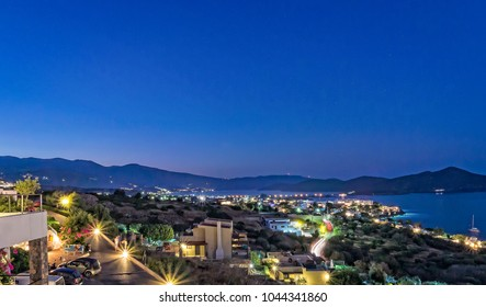 A nighttime view towards the town of Elounda in Crete, with a variety of differing lights.