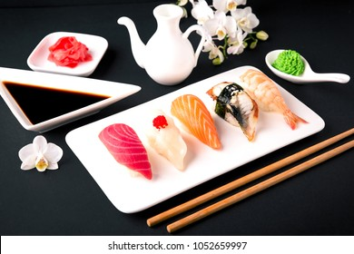 Nigiri with salmon, tuna, perch, eel, scallop, caviar, shrimp, sharp. Gunkan sushi set.   Traditional Japanese cuisine. Black background. Beautiful geometric  food style