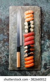 Nigiri Sushi and Japanese knife on stone slate background