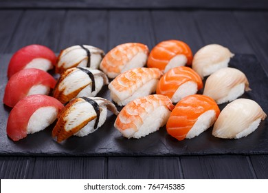 Nigiri sushi with salmon, grouper, eel, tuna and prawn, served on black stone slate. Delicious traditional Japanese food, tasty seafood, restaurant concept, food background