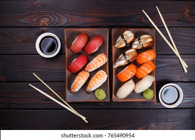 Nigiri sushi with salmon, grouper, eel, tuna and prawn on clay plates with soy sauce and chopsticks, flat lay. Delicious traditional Japanese food, tasty seafood, restaurant concept, food background