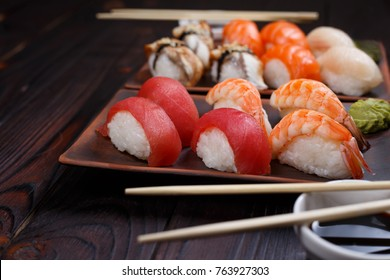 Nigiri sushi set served on clay plates with soy sauce and chopsticks, close up. Delicious traditional Japanese food, tasty seafood, sushi restaurant concept