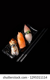Nigiri Sushi Set of Unagi Eel, Sake Salmon, Tai Sea Bream Perch served on black plate, chopsticks and background.  Traditional Japanese cuisine. Wallpaper