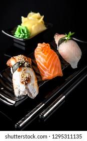 Nigiri Sushi Set of Unagi Eel, Sake Salmon, Tai Sea Bream Perch served on black plate, chopsticks and background.  Traditional Japanese cuisine. Wallpaper