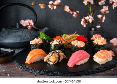 Nigiri with Tuna, Salmon, Eel and Shrimp. Gunkan sushi set.  Dish decorated with a sprig of cherry blossoms. Traditional Japanese cuisine
