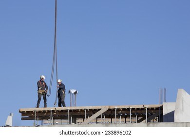 NIJKERK, NETHERLANDS, 24 NOVEMBER 2014: construction workers on roof of new building with blue sky