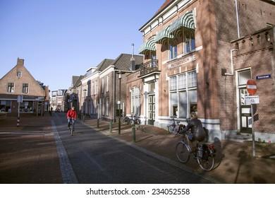 NIJKERK, NETHERLANDS, 24 NOVEMBER 2014: street with people on bicycle in the dutch town of Nijkerk