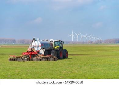 NIJKERK, NETHERLANDS - MARCH 2, 2019: Tractor with liquid manure injector fertilizing a meadow