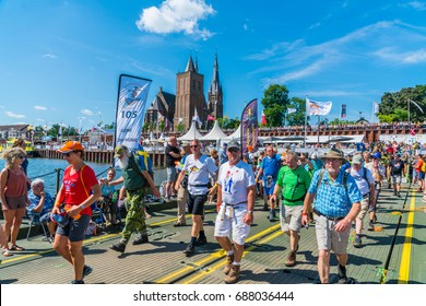 Nijmegen July 20 2017: 4Day Walking tournament contestants passing the church of the Village Cuijk