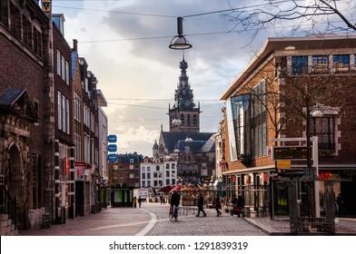 NIJMEGEN, NETHERLANDS - APRIL 10, 2010: The tower of the Stevenskerk church in the Dutch city of Nijmegen. People walking in the street. Holland. Europe.