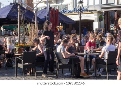 Nijmegen, Netherlands - April 19, 2018: Waitress serves drinks to people that relax and enjoy a drink at an outdoor cafe terrace