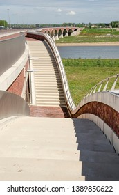 Nijmegen, The Netherlands, April 25, 2019: concrete staircases lead down from bridge De Oversteek to the floodplains and the new river channel