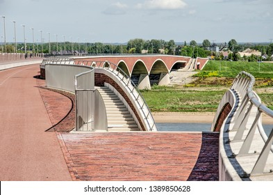 Nijmegen, The Netherlands, April 25, 2019: elegantly curving staircases lead down from the bridge deck of De Overstek to the landscape park in the floodplain