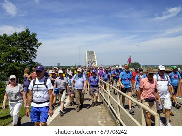 Nijmegen, Netherlands, July 2017. participants of the Nijmegen four days marches have crossed the bridge over the river and are on their way to the finish