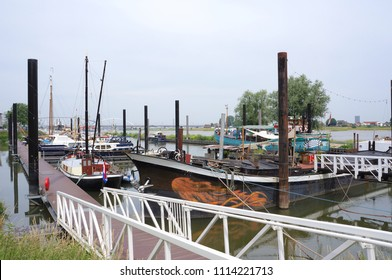 Nijmegen, the Netherlands. June 2018. Several old boats in a harbor near Nijmegen in the Netherlands with the Waalbrug bridge in the background.
