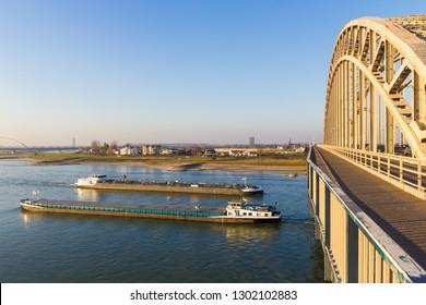 Nijmegen, the Netherlands - November 16 2018: cargo river barges passing under waal bridge in Nijmegen during time of low river levels