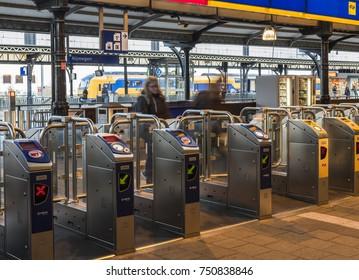Nijmegen, Netherlands - November 7, 2017: OV-gates at railway central station Nijmegen with travelers and trains at the platform.