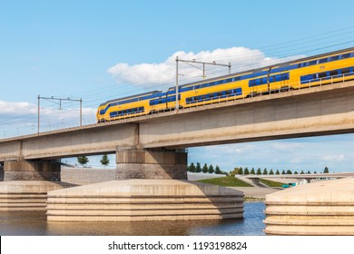 NIJMEGEN, THE NETHERLANDS - SEPTEMBER 1, 2018: Dutch train crossing the sideskirts of the river Waal in front of the city of Nijmegen, The Netherlands