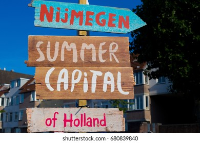 Nijmegen summer capital of Holland. Hand-painted wooden signs with city background. Nijmegen, The Netherlands, July 2017.