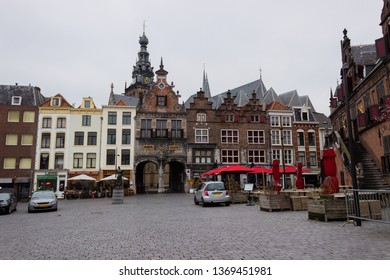 Nijmegen/The Netherlands - January 27 2018: Restaurants that line the courtyard outside St Steven's Cathedral with a statue of The Lady of Nijmegen