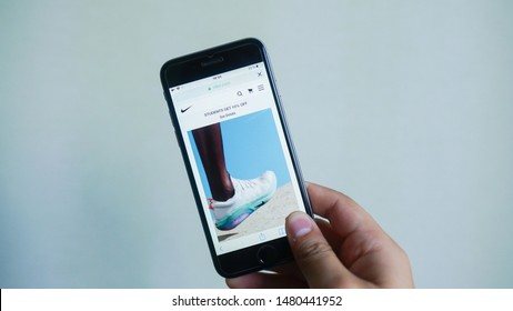 Nike website homepage. Nike logo visible on the iphone screen. Nike, Inc. - An American multinational company specializing in sportswear and shoes. Los Angeles, California, USA - 16 August 2019