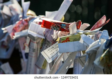 Nikko, Japan - December 20. 2017: Omikuji (fortune-telling paper strip) tied to a rope at a Japanese temple in Nikko, Japan.
