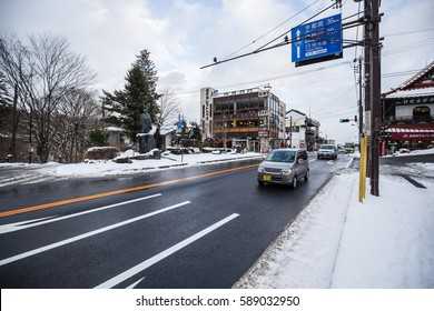 Nikko, JAPAN - January 17, 2017: moving car at the street local road in the village in Nikko japan in the winter with snow on the sidewalk