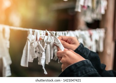 NIKKO, JAPAN - OCT 12,2018 : Close up of an unidentified girl's hands puts messages with the wishes Omikuji Paper Fortune at japan Temple.