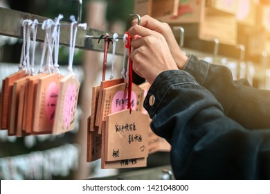 NIKKO, JAPAN - OCT 12,2018 : Close up of an unidentified girl's hands puts small wooden plaques with the wishes at japan Temple.