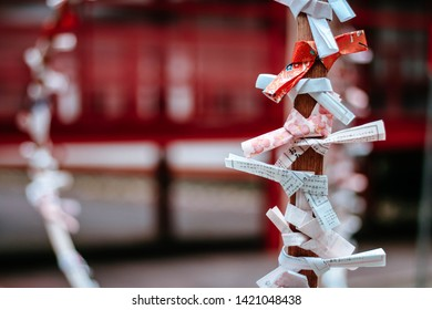 NIKKO, JAPAN - OCT 12,2018 : Talismans, Japanese fortune paper are wrapped in a rope at a Japanese temple.