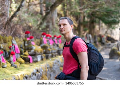 Nikko, Japan and young happy man looking at Jizo statues in famous Kanmangafuchi Abyss in Tochigi prefecture in Japan in early spring
