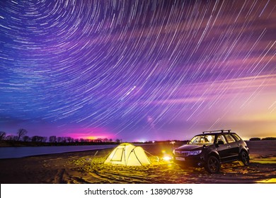 NIKOLAEVKA, RUSSIA - MAY 03, 2019: Night camping at the river. Star trails in the sky. Subaru Forester stands near the tent