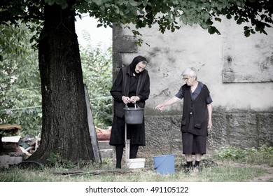NIKSIC, MONTENEGRO - JULY 25, 2016: two old women in black dresses are filling some buckets with the water of a faucet outdoor under a big tree