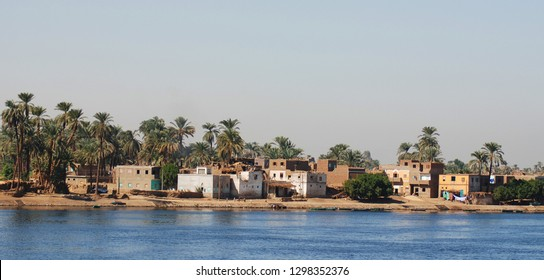 NILE RIVER BANK EGYPT NOV 25 2008: Village on Nile river shore countryside landscape with african houses on riverbank