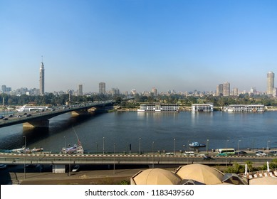 Nile River on its way through the city of Cairo, Egypt with boats moored on the shore and view of modern buildings of the city