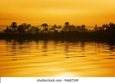 Nile view at sunset with tropical palm tree silhouette and distant mountains