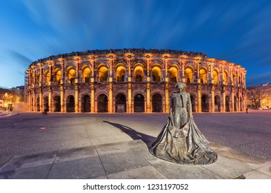 Nimes, France - 14 December 2018: Roman amphitheater (Arena of Nimes) at dusk and monument to bullfighter