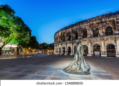 Nimes, France: July 2, 2018 - Bronze statue of bullfighter Nimeno II in front of the ancient Roman amphitheatre.