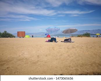 Nin Dalmatia, Croatia - July 8, 2019: Sandy beach in summer. Tourists rest and bathe in the sea. Adriatic town, sandbar Queen's beach in Nin, near salt producing pans. Velebit mountain in background.