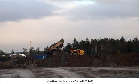 Ninashamn, Sweden - Nov 21, 2018: articulated dump truck Caterpillar 740B unload at the work site