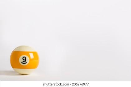 Nine ball on a plain white background lower left corner.