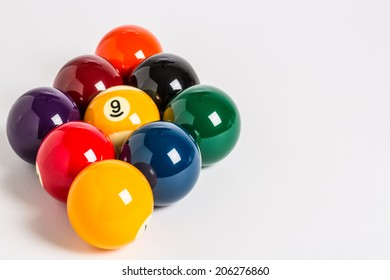 Nine Ball racked in a diamond shape on a plain white background left side with cue stick, chalk and cue ball in foreground.