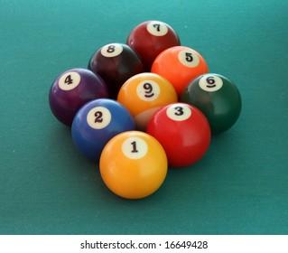 nine billiard balls on the green table