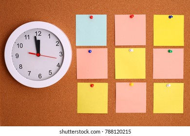 Nine color note card and white clock on cork board. Free space in text.