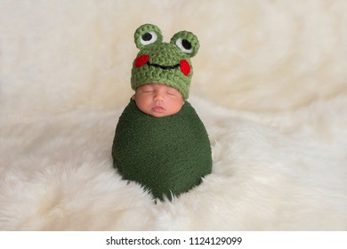 Nine day old newborn baby boy wearing a green frog hat. He is sleeping upright while swaddled in a stretch wrap.