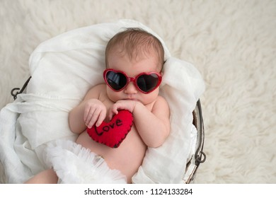 "Nine day old, newborn baby girl wearing red, heart shaped sunglasses. She is holding a heart shaped pillow with the word, ""Love"" written on it."