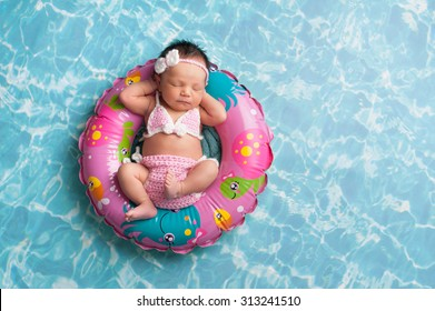 Nine day old newborn baby girl sleeping on a tiny inflatable swim ring. She is wearing a crocheted pink and white bikini.